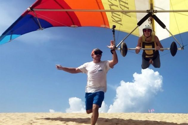 Kitty Hawk Kites hang gliding school manager teaching someone how to hang glide